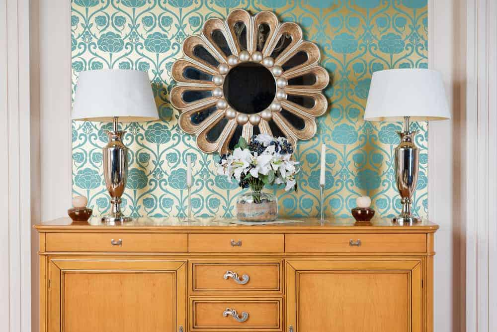This is a close look at an art deco hollywood glam style decoration with a wooden console, patterned wallpaper and a large mirror in between two golden lamps.