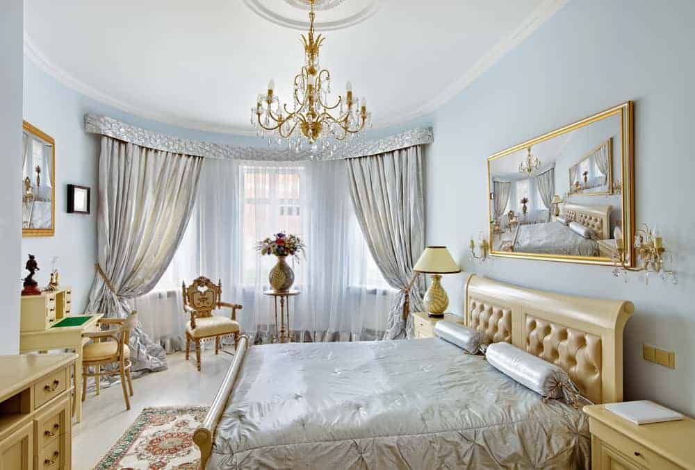 This is an elegant hollywood glam-style bedroom with light pastel blue walls, a beige sleigh bed and golden chandelier.