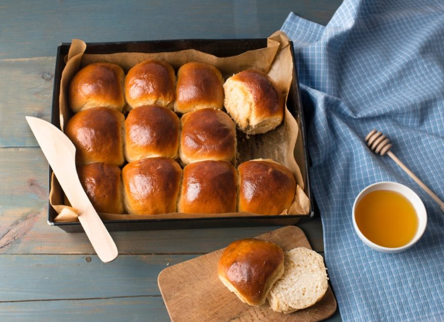 A batch of freshly-baked honey buttered dinner rolls on a wooden table.