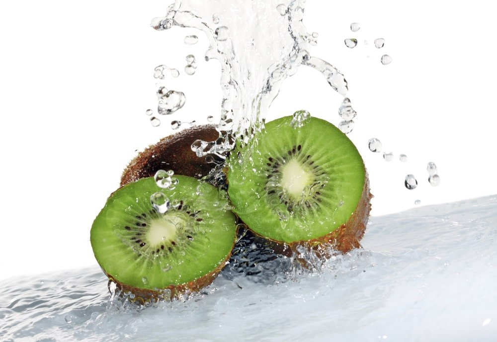 This is a close look at pieces of kiwi fruits being washed.