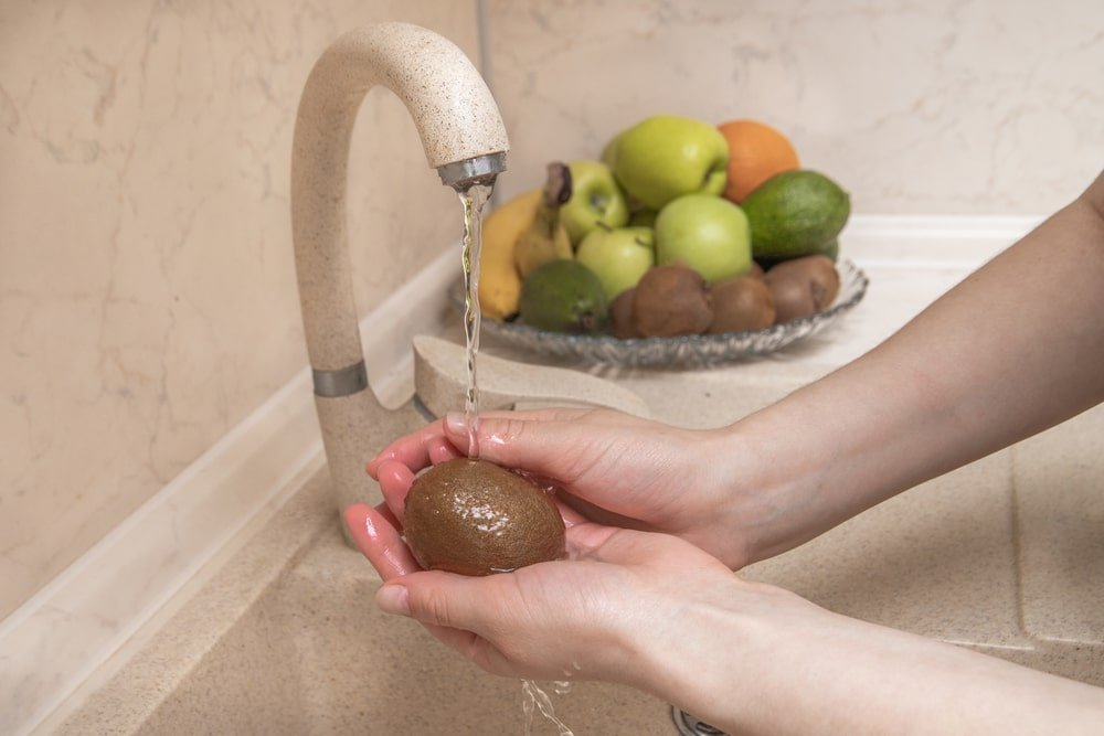 A close look at a woman washing a piece of kiwi.