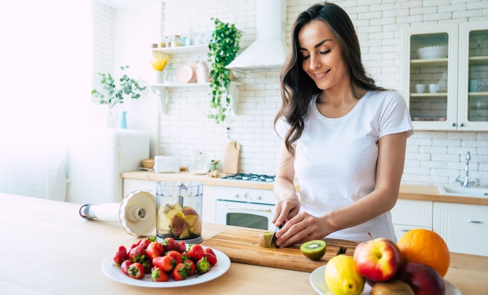 A close look at a woman slicing fruits in the kitchen.