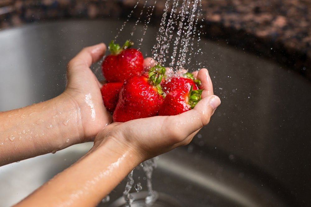 A handful of strawberries being washed.