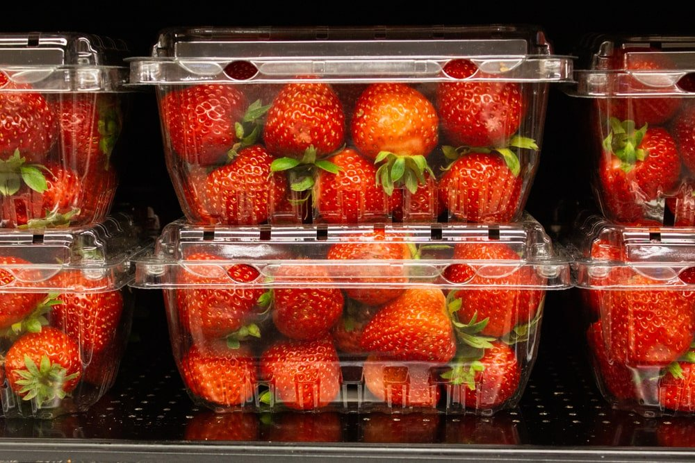 Ripe strawberries stored in plastic containers on display.