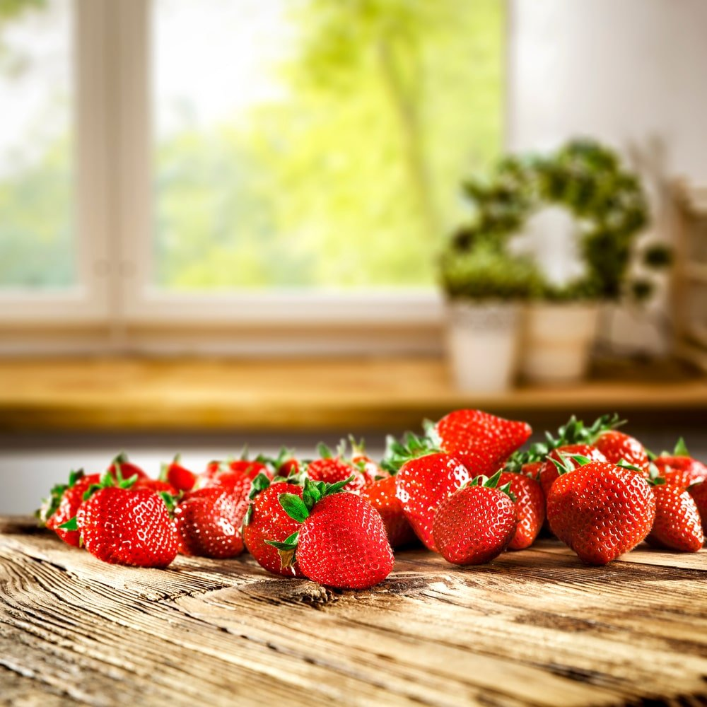 A bunch of ripe strawberries on a wooden countertop.