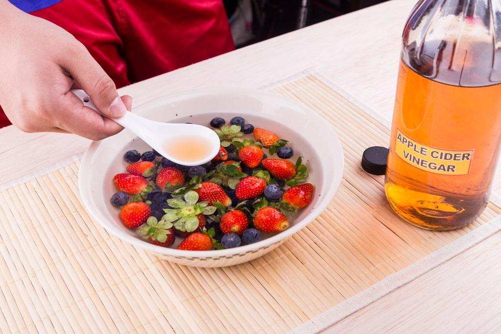 A bowl of berries undergoing vinegar bath.