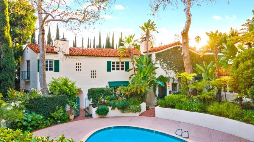 This is an exterior view of the back of the house that has beige walls, terracotta roof tiles, green accents and lush landscaping of tropical trees, shrubs and a large pool. Image courtesy of Toptenrealestatedeals.com.