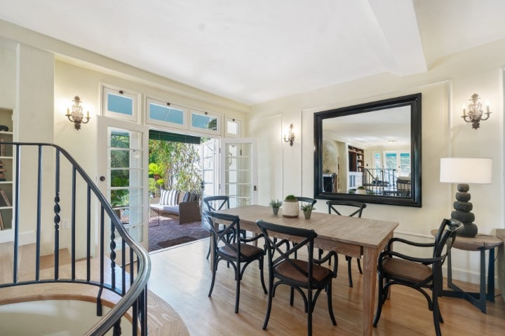 This is a close look at the dining area with a rectangular wooden dining table surrounded by black chairs that match the frame of the wall-mounted mirror. Image courtesy of Toptenrealestatedeals.com.