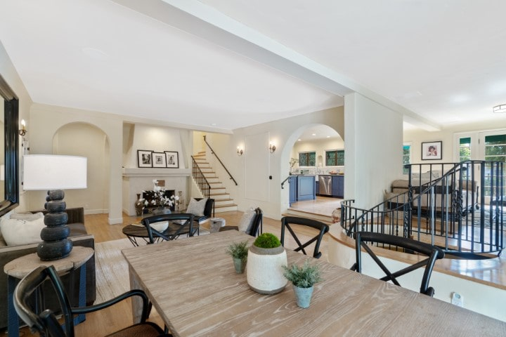 This is a view of the large open room that houses the dining area and living room with a view of the stairs and arches that lead to the other sections of the house. Image courtesy of Toptenrealestatedeals.com.