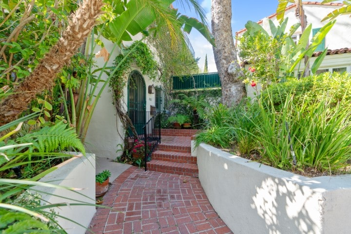 This is the walkway entrance to the villa with terracotta flooring, beige concrete planters and tropical plants and trees for shade. Image courtesy of Toptenrealestatedeals.com.