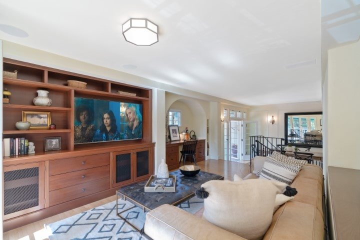 The family room has a large comfortable beige sectional sofa and coffee table across from the large wooden structure that houses the TV. Image courtesy of Toptenrealestatedeals.com.