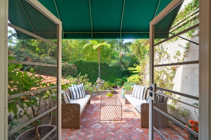 Through the French doors is the patio with a couple of large outdoor sofas, a coffee table and terracotta flooring tiles with a herringbone pattern. Image courtesy of Toptenrealestatedeals.com.