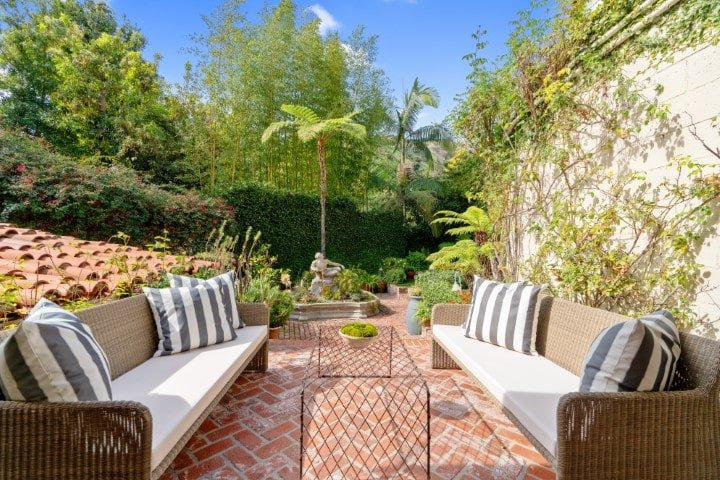 This is a closer look at the patio that complemented by the lush landscaping of tropical trees, plants and shrubs in the background. Image courtesy of Toptenrealestatedeals.com.