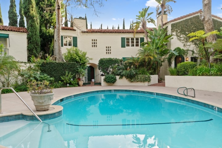 This is the view of the shared Hollywood-style pool of the villas surrounded by beige concrete structures and tropical landscaping with colorful shrubs and tall trees. Image courtesy of Toptenrealestatedeals.com.