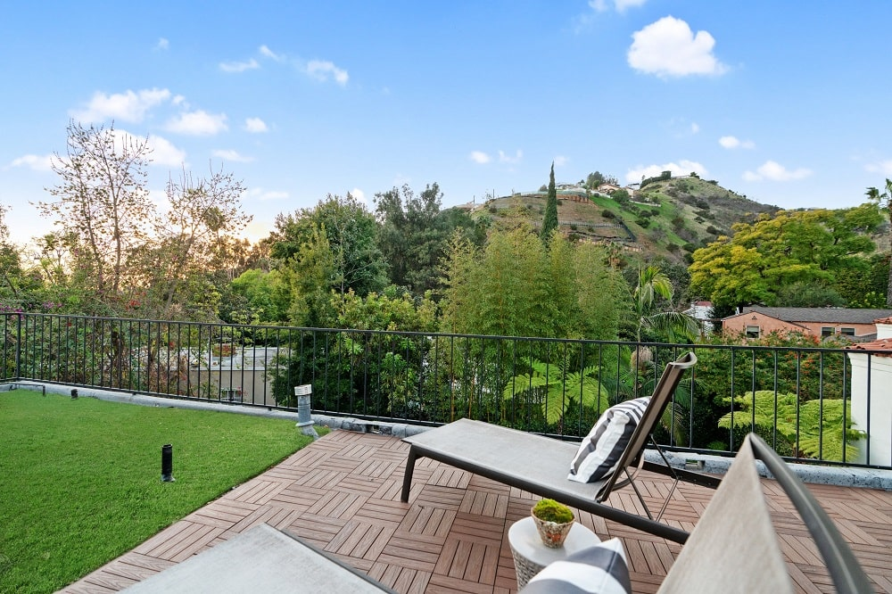 This is the rooftop terrace that has lounge chairs on terracotta flooring tiles bordered with wrought iron railings and a view of the surrounding treetops. Image courtesy of Toptenrealestatedeals.com.