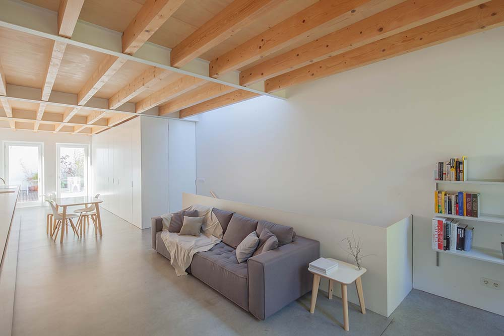 This is a full view of the minimalist living room that has a simple gray sofa paired with white walls with built-in structures and a wooden ceiling above that has exposed beams.