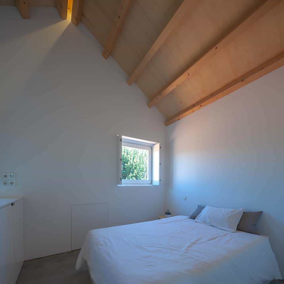 This is a look at the minimalist bedroom that has a white bed to match the white walls topped iwth a wooden cathedral ceiling with exposed beams.