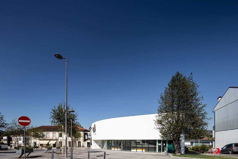 The bright white exterior walls and glass walls of the bank are complemented by the tall trees.