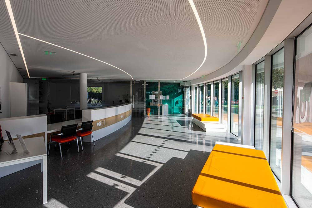 This is a view of the bank interior brightened by the glass walls and has multiple seating.