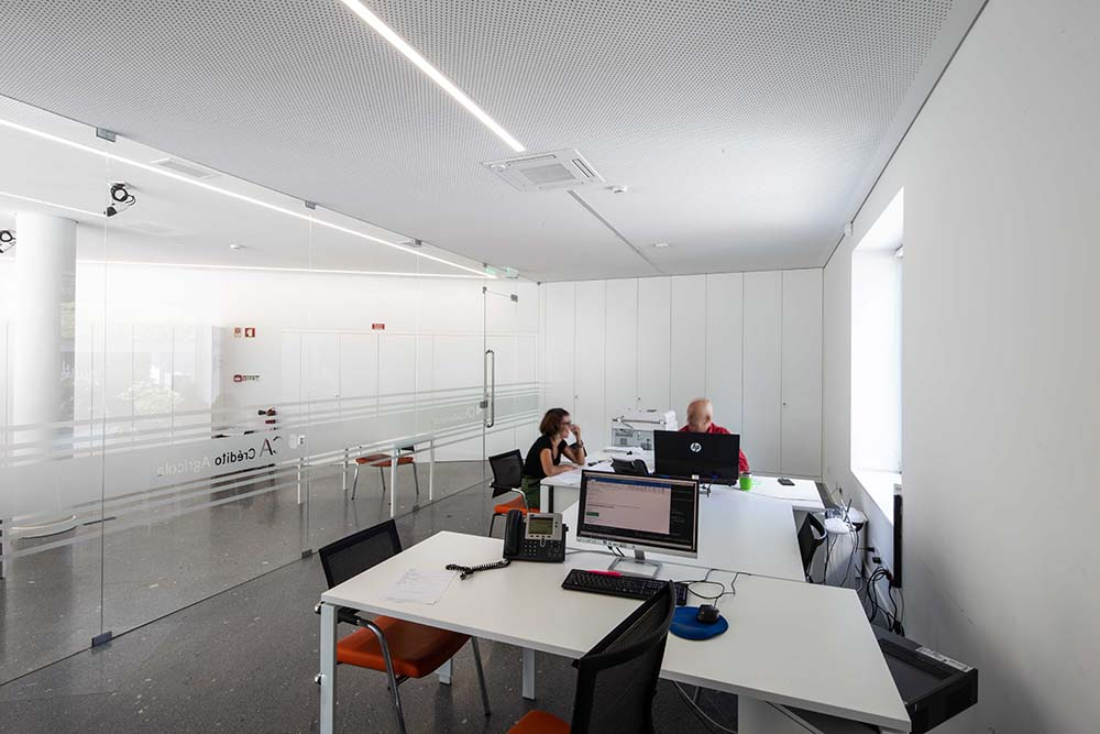 Beyond the glass wall of the lobby is this small office with modern white desks.