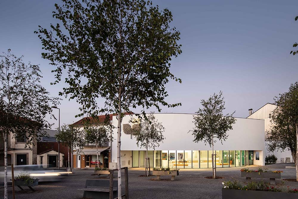 The warm glow of the glass walls on the ground level matches well with the white exterior walls of the upper level.