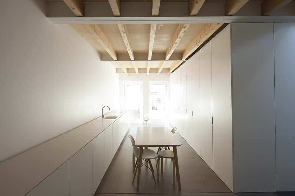 This is a long and narrow eat-in kitchen with a minimalist design of white cabinetry on both sides topped with a wooden beamed ceiling and a small table in the middle.