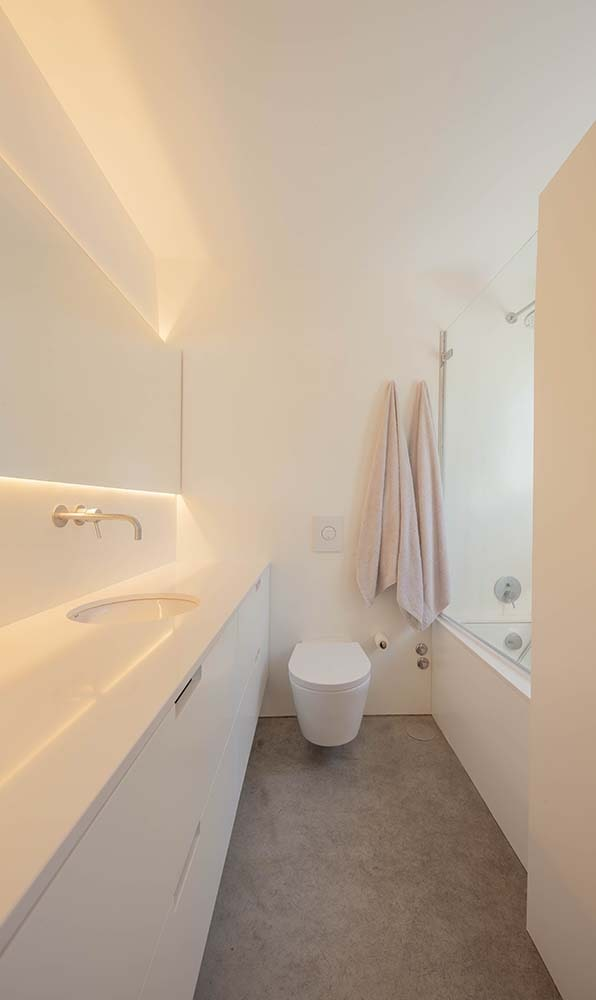 The bright white bathroom has a white sink across from the white shower area and bathtub with the toilet on the far side.
