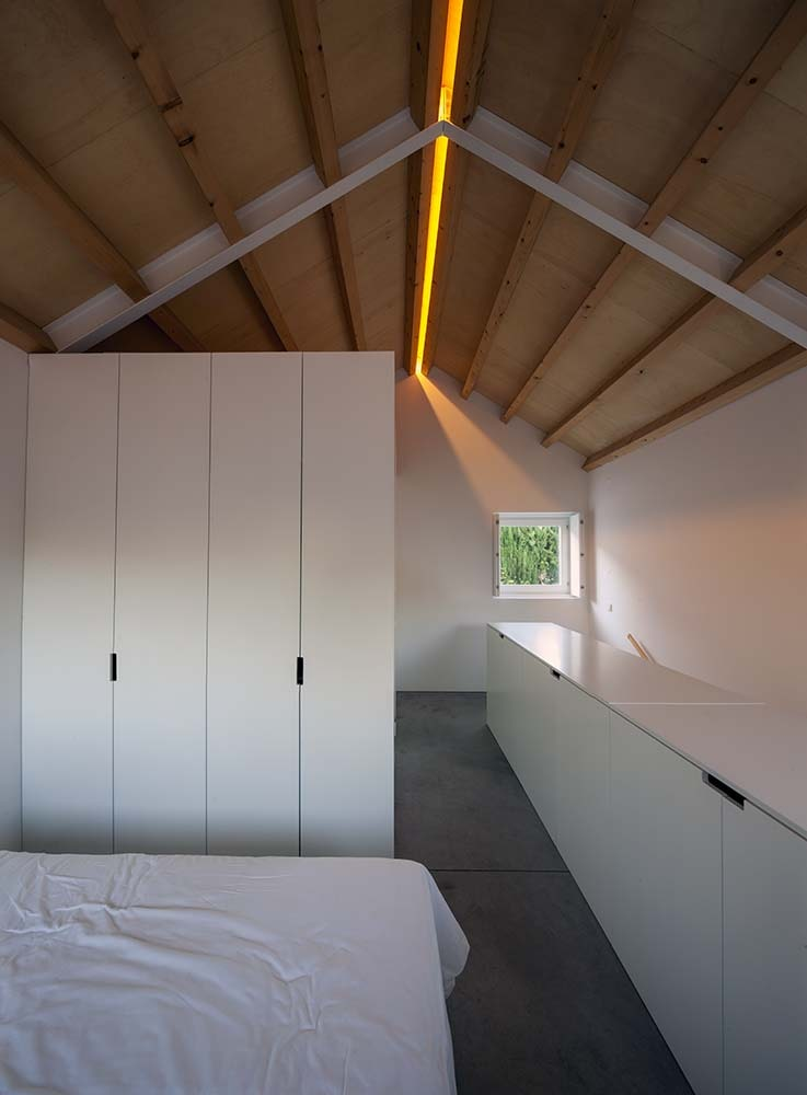 The bedroom has a white bed paired with a white modern cabinet and a tall cathedral ceiling with exposed beams.
