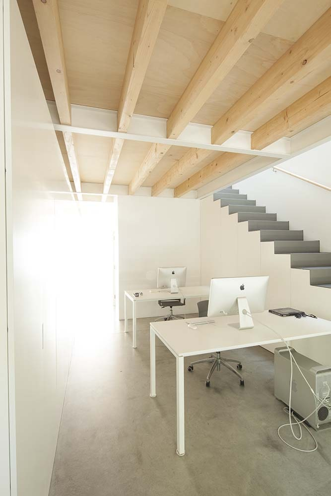 At the level below is a home office area on the side of the staircase witha couple of white modern desks.