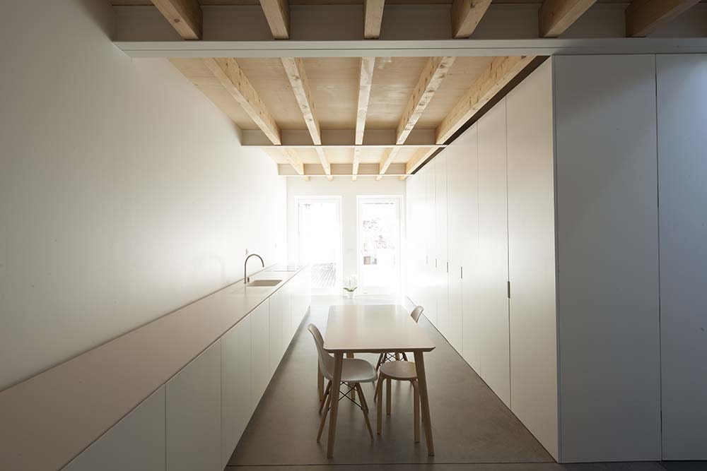 This is a close look at the dining area with a rectangular dining table and a set of modern built-in cabinets on the other side.