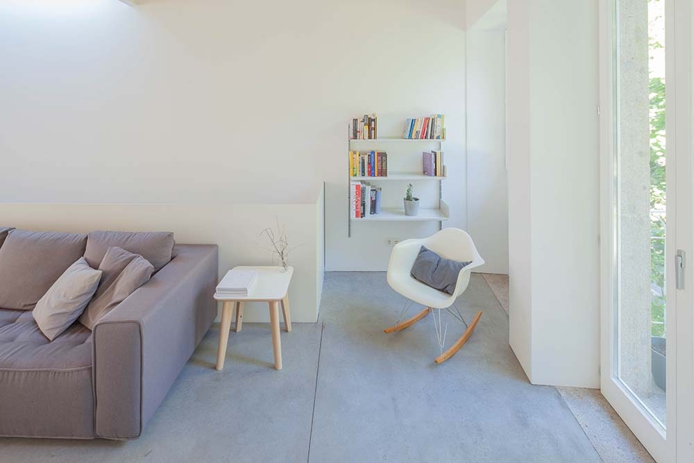 This is a close look at the side of the sofa with a reading nook and small library that has a small bookshelf on the far side.