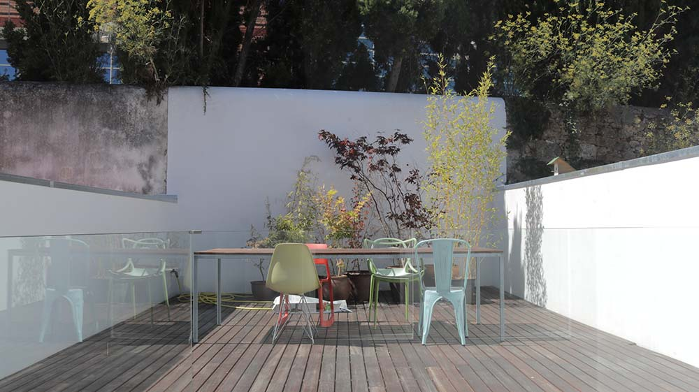 On the far side of the terrace deck is a set of various potted plants that bring color to the area.