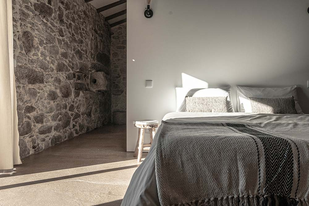 This other bedroom has a large bed with a bedside table and a wall made of stone on the side.