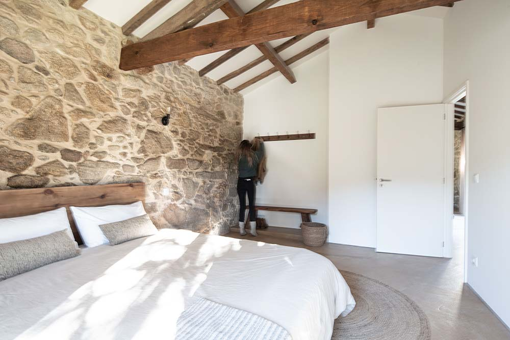 The bedroom is topped iwth a cathedral ceiling that has rustic wooden beams.
