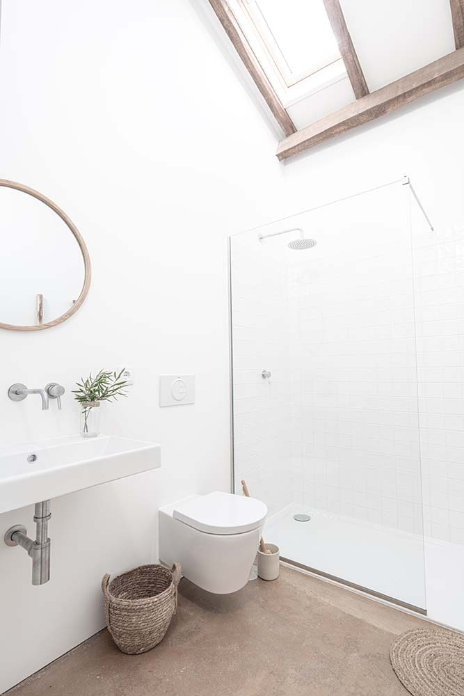 The bathroom has a consistent bright beige tone on its walls and ceiling. It has a glass-enclosed shower area on the far side.