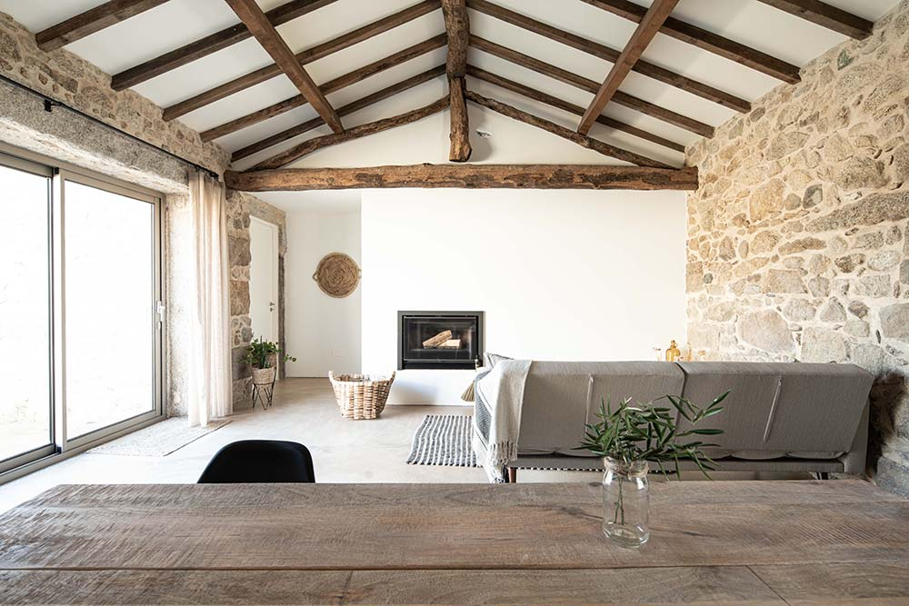 This is an interior view of the house with a living room topped with a cathedral ceiling that has rustic exposed beams.