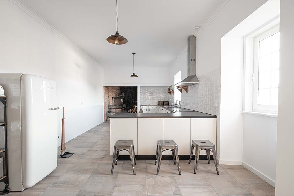 This is a look at the kitchen with an L-shaped peninsula paired with small stools for a breakfast bar.