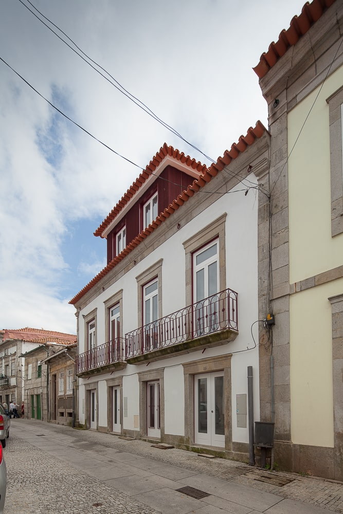 This is another street view of the house that showcases the row of glass windows on the first level and the matching row of glass windows on the upper level that pair well with the white exteriors contrasted by the red clay tile roof.