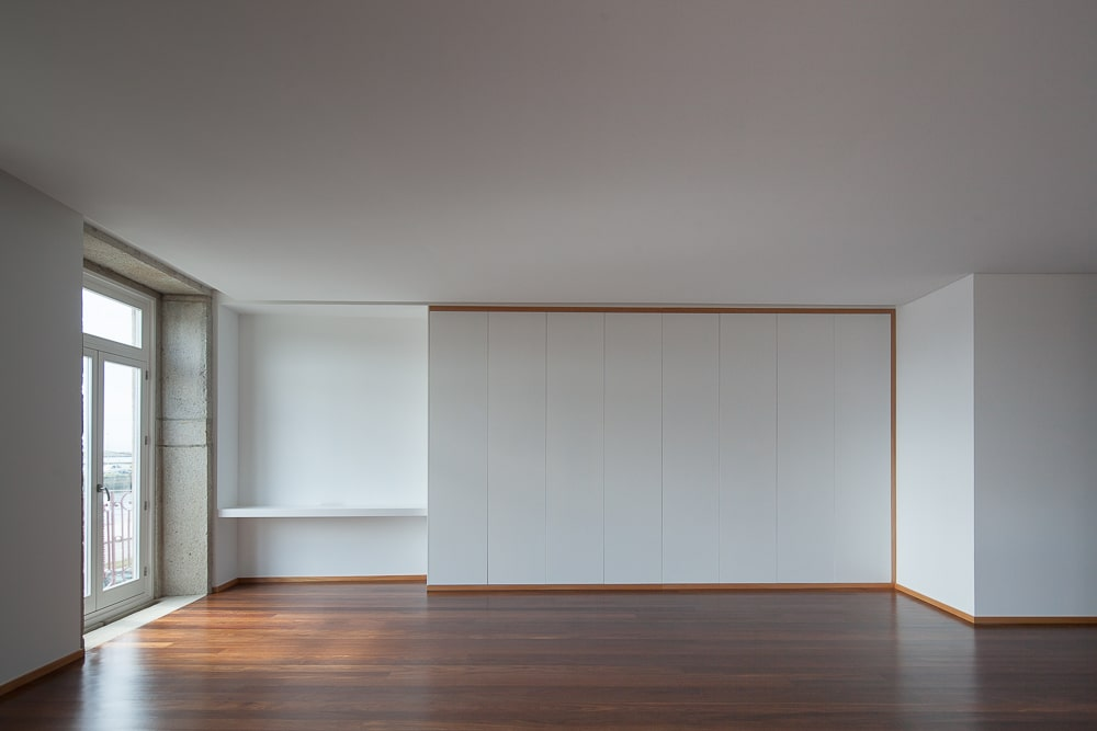 This is a close look at the large white wall with a built-in desk on the far corner beside the window for a study area.