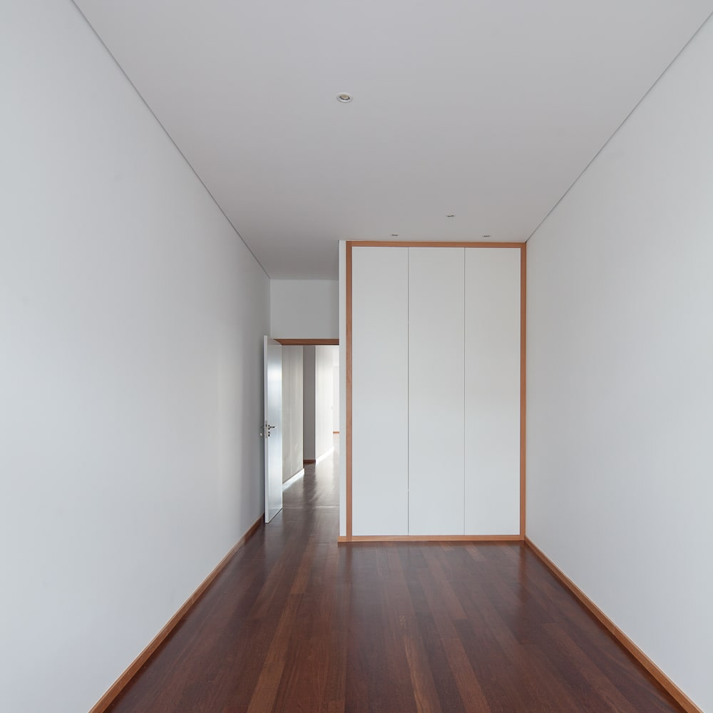 This is a close look at the hallway that has a hardwood flooring, an entryway on the far side and a large white cabinet built into the wall.