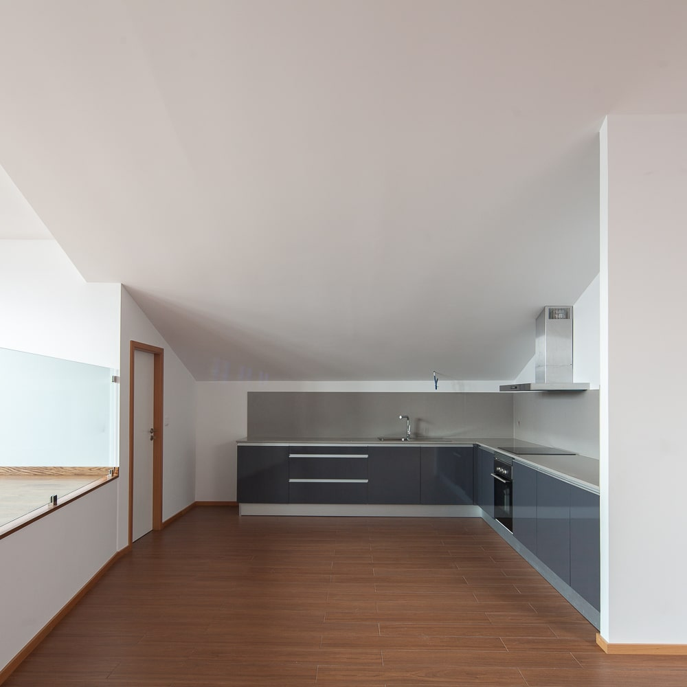 This is a closer look at the kitchen with its modern gray cabinetry that stands out against the white walls and white ceiling.