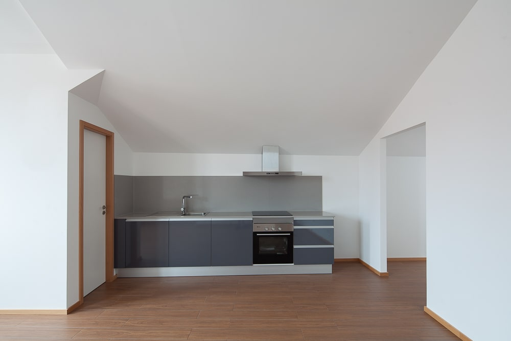 This is a close looka t the small kitchen with modern gray cabinetry and appliances that stand out against the white walls and hardwood flooring.
