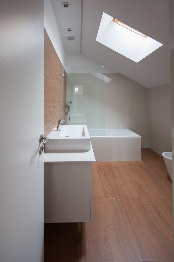 The bathroom has a bathtub on the far side on the side of the vanity that is topped with a skylight.