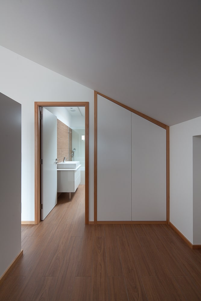This is a close look at the bathroom door with a set of built-in cabinets on the side following the lay of the wall and ceiling.