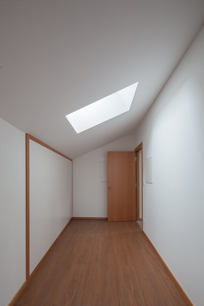 This room has white walls, white shed ceiling and hardwood flooring complemented by the skylight.