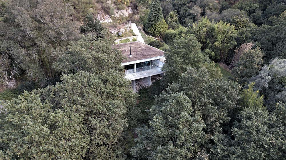 This is an aerial view of the house that is complemented by the surrounding landscape of tall trees.