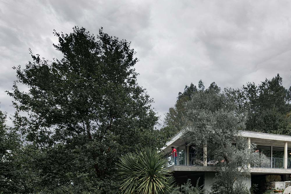This is a farther view of the house that is almost hidden behind the thick foliage of trees.
