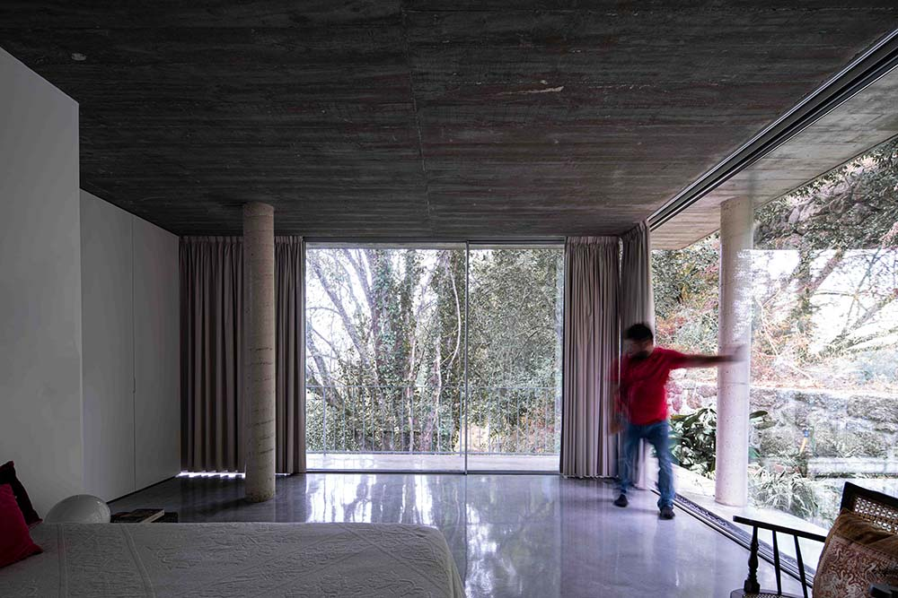This is a close look at the interior of the house with glass walls on two sides looking out to the surrounding tall trees.
