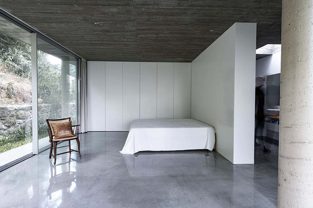 The shiny gray floor of the bedroom contrasts with the dark concrete matte ceiling.