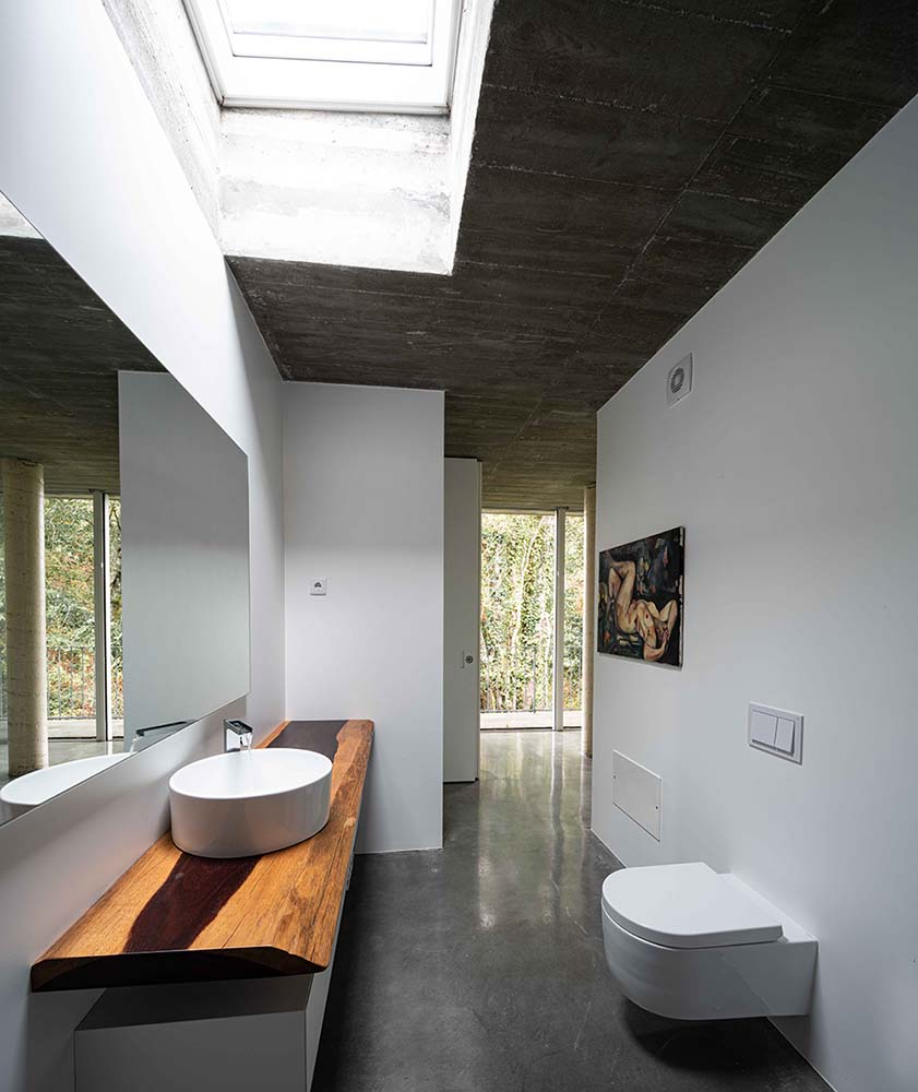 This is the bathroom with a rustic wooden vanity across from the modern floating toilet.